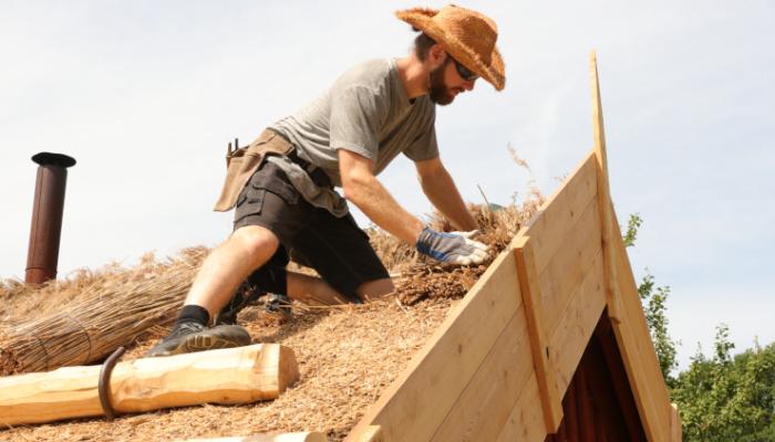 En byggnadsvårdare lägger vasstak