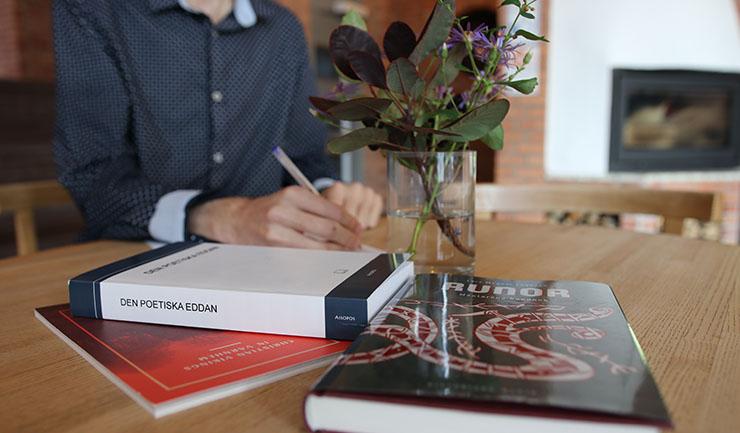 Person skriver vid kafébord